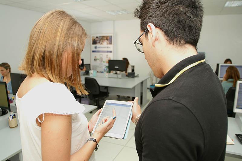 dos personas mirando una pantalla en una oficina
